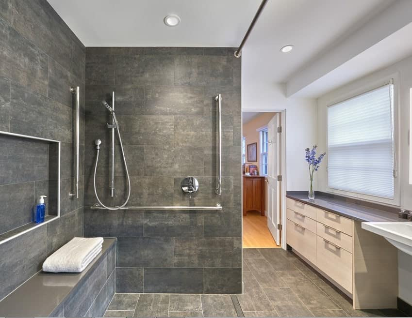 This bathroom features black tiles walls matching the flooring. The open shower is placed in the corner in front of the sink and lovely bathroom counter.