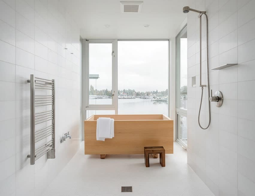 This primary bathroom offers a wooden bathtub surrounded by white walls and floors. The tub is placed near the glass windows overlooking the beautiful surroundings.