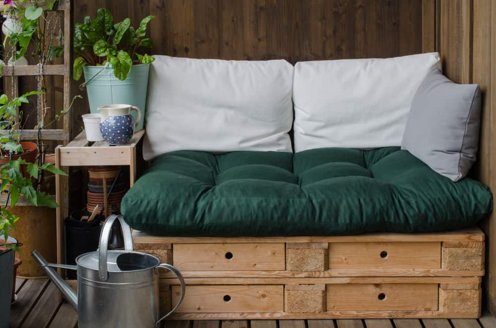 Small patio pallet couch with white pillows and green seat cushion