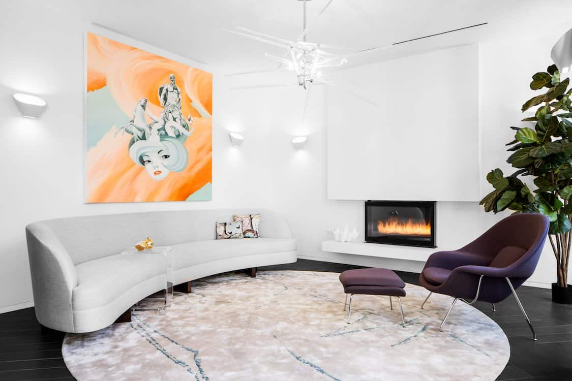 Cool white living room with curved modern sofa and fireplace by DÉCOR AID
