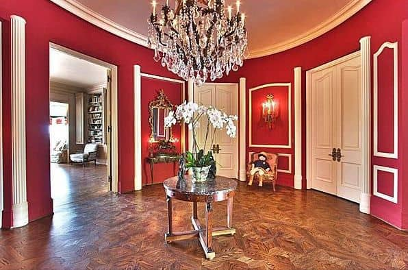 This elegant and large foyer has curved red walls that make the white wall accents stand out as well as the white doors. This is paired with a large crystal chandelier in the middle hanging over a small round silver table bearing white flowers in a pot.