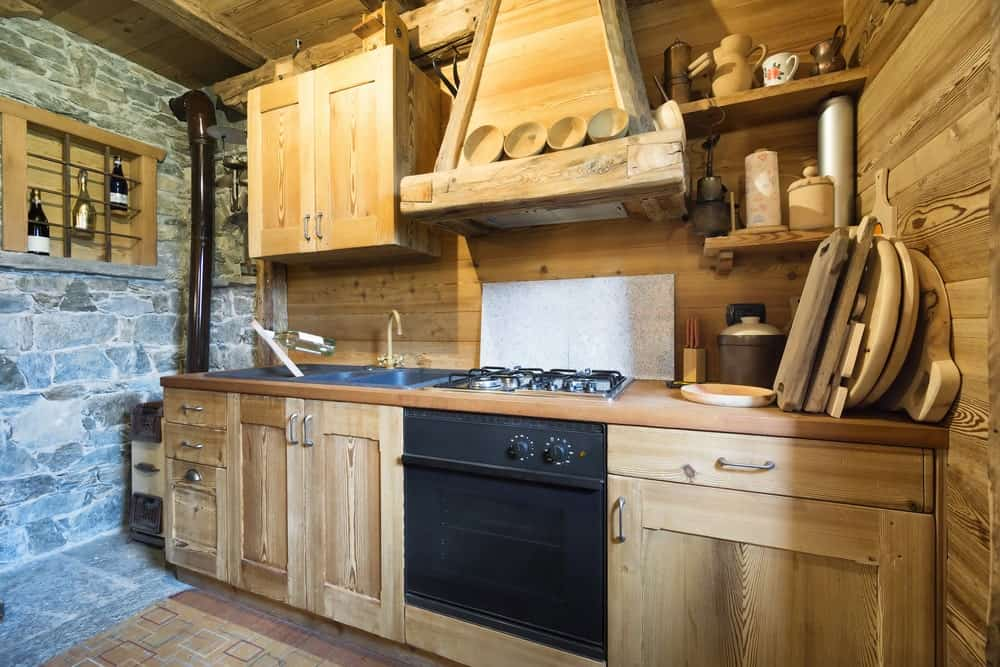 This rustic kitchen features a stylish stone wall on the left side near the sink. There's also a tiny wine cellar on the corner.