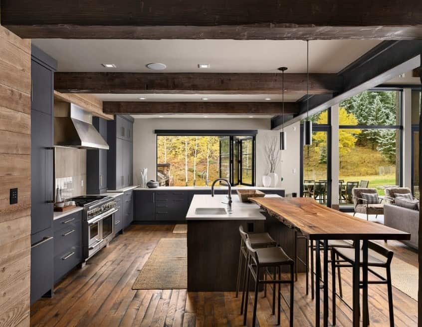 Large kitchen with a hardwood flooring and beams ceiling. The gray counters look stylish. Both counters and center island boasts smooth white countertops.