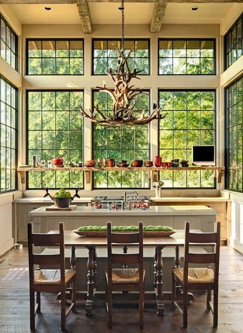 This kitchen features a hardwood flooring and a tall ceiling lighted by a jaw-dropping chandelier.