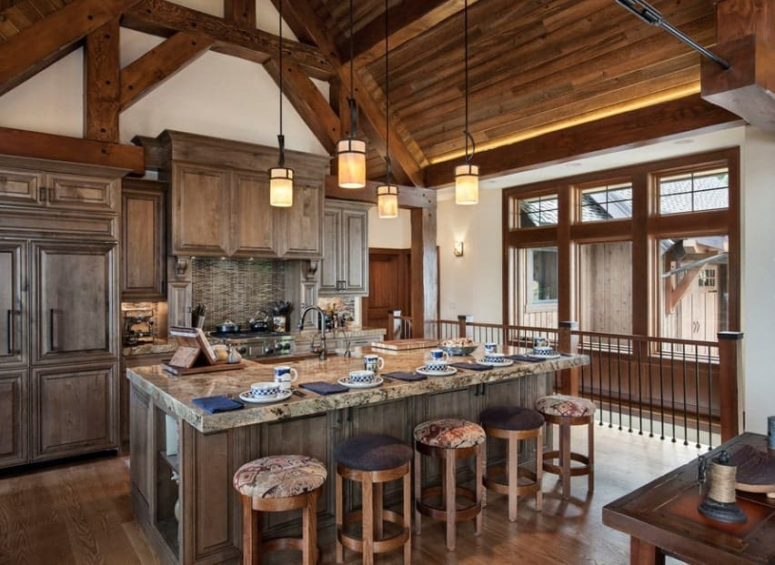 Large rustic kitchen with a large center island with a marble countertop. The tall ceiling looks stunning along with its pendant lighting.