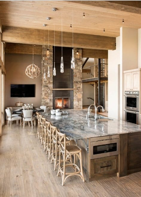 This rustic kitchen boasts a massive center island with stylish marble countertop lighted by pendant lights. There's a brick fireplace too near the dining nook.