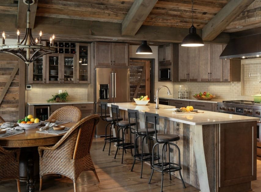 Rustic kitchen with a large center island with a smooth countertop lighted by pendant lights.