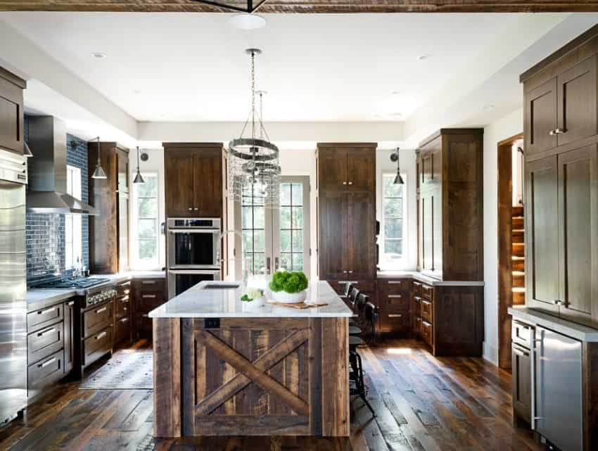 This kitchen features hardwood flooring and rustic cabinetry and center island equipped with a white marble countertop. The ceiling light looks stylish.