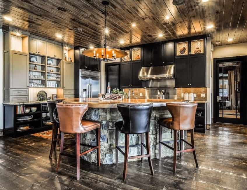 Stunning rustic kitchen featuring a stunning ceiling lighted by recessed lights and candlelight chandelier. The flooring and center island look so stylish as well.