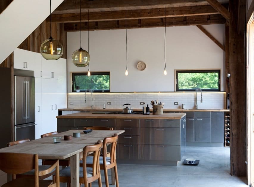 This kitchen boasts wooden countertops on both counters and center island. The rustic ceiling looks magnificent while the lighting looks perfect with the kitchen's style as well.