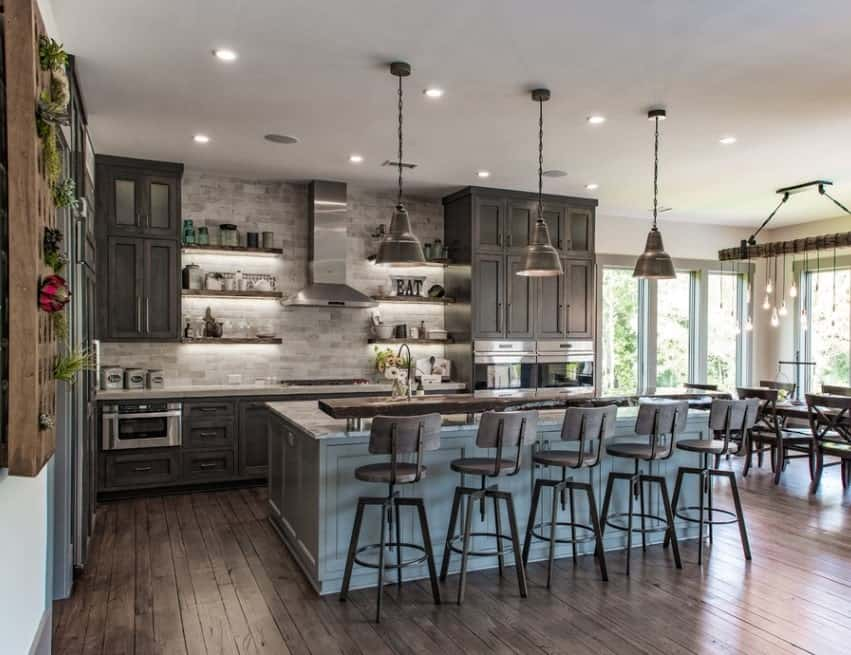 A classy kitchen boasting rustic finish from flooring to counters and cabinetry. There's a large center island with a marble countertop along with a breakfast bar lighted by pendant lights.