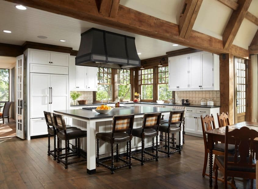 Large kitchen featuring a massive center island with dark finished countertop and bar stools, all set on the hardwood flooring.