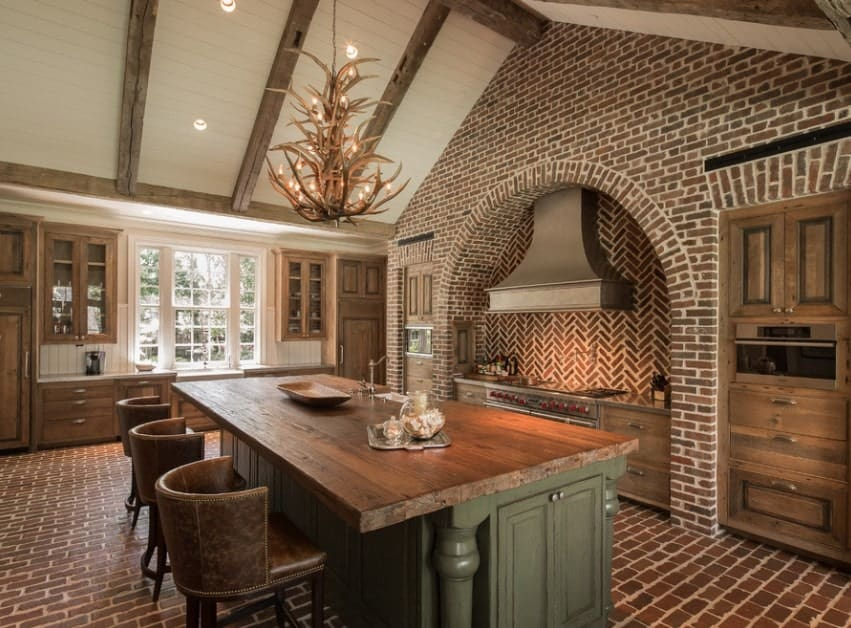 Elegant kitchen featuring tiles flooring and rustic cabinetry. There's a large center island providing space for a breakfast bar lighted by a glamorous chandelier.