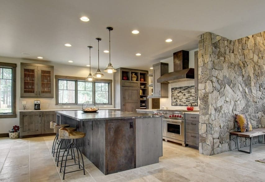 This kitchen boasts rustic cabinetry and center island with a stylish countertop. The whole kitchen is lighted by recessed and pendant lights.