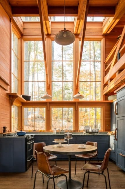 Rustic kitchen with tall ceiling and glass windows. The counters are finished with black adding style to the area. There's a dining nook on the center lighted by pendant lights.