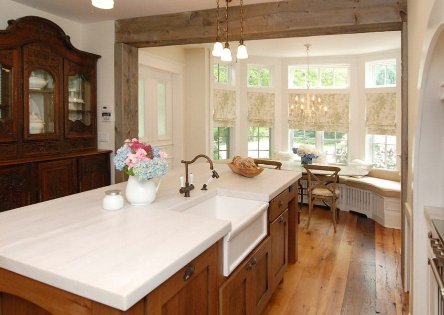 This kitchen features white walls and hardwood flooring along with a center island equipped with white smooth countertop lighted by pendant lights.