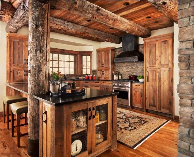 Stunning rustic kitchen with walnut finished cabinetry and counters featuring black countertops. The rug looks very elegant as well.