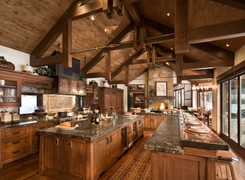Large rustic kitchen featuring a large center island with granite countertop. There's a long breakfast bar too.