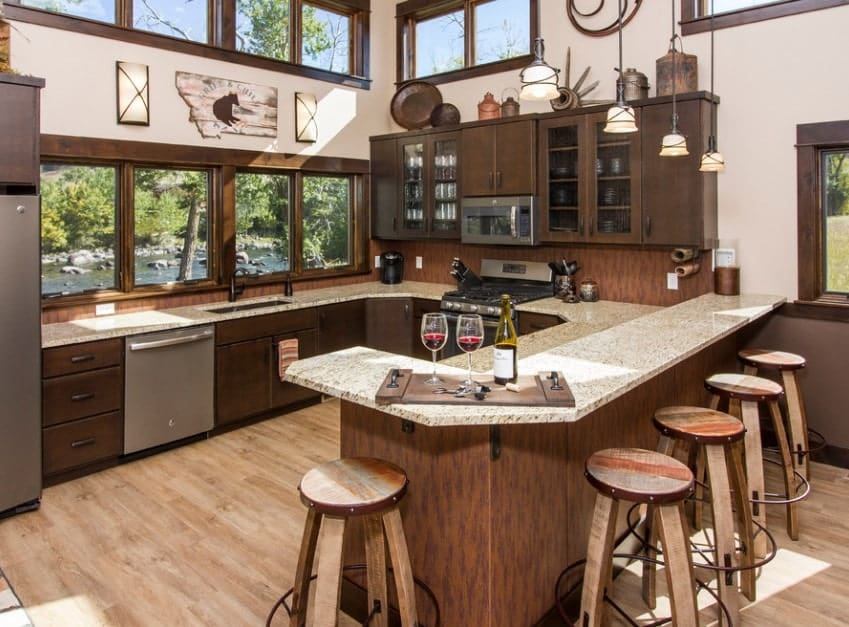 Large kitchen featuring brown finished cabinetry and counters. The marble countertops look glamorous lighted by pendant lights.