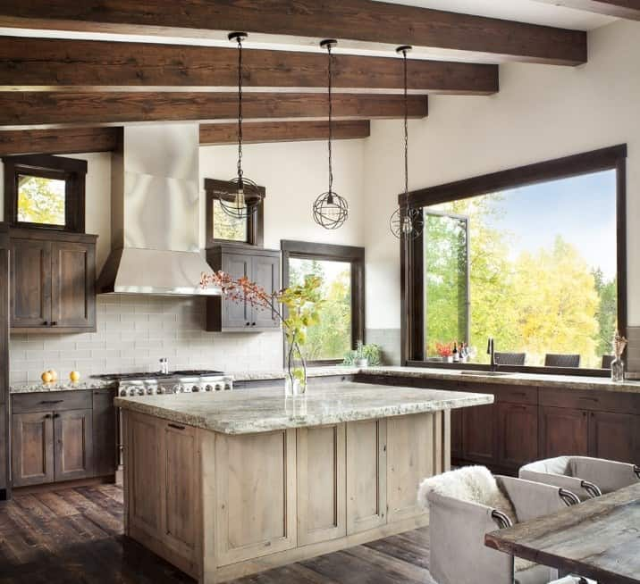 Vintage style rustic kitchen with a large center island lighted by pendant lights.