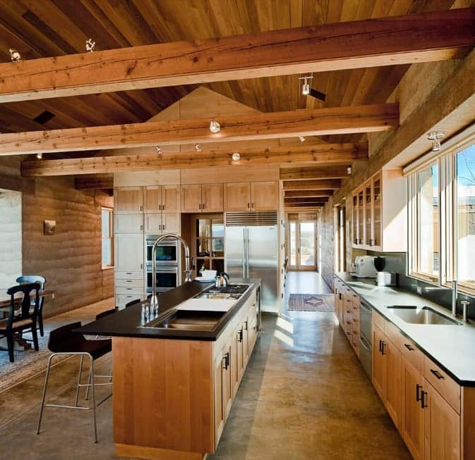 This kitchen features rustic finish all over the place. The countertops on both counters and center island are finished with dark paint for additional style.