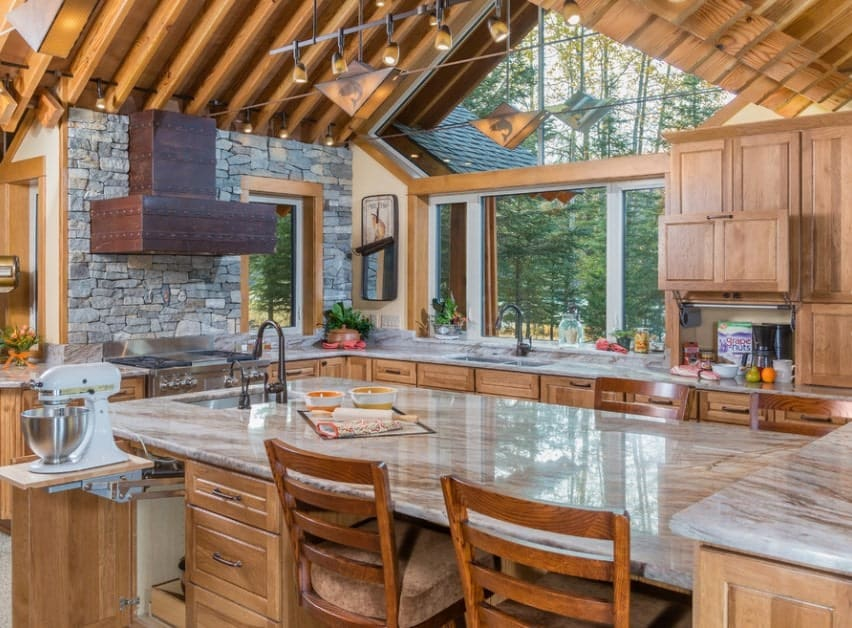 Large rustic kitchen with walnut finished cabinetry and counters along with a massive center island featuring a marble countertop.