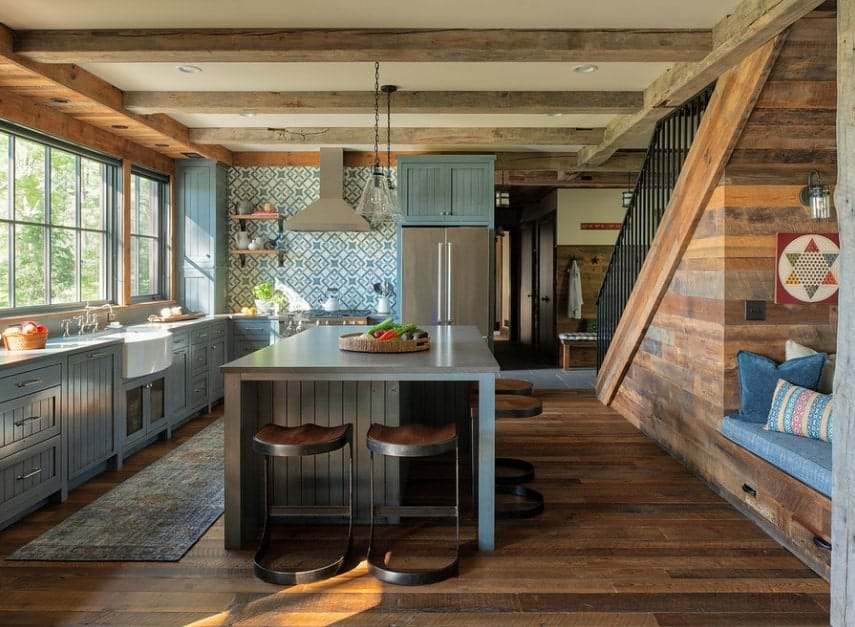A rustic open kitchen featuring a hardwood flooring topped by a rug. There's a center island as well providing space for the breakfast bar.