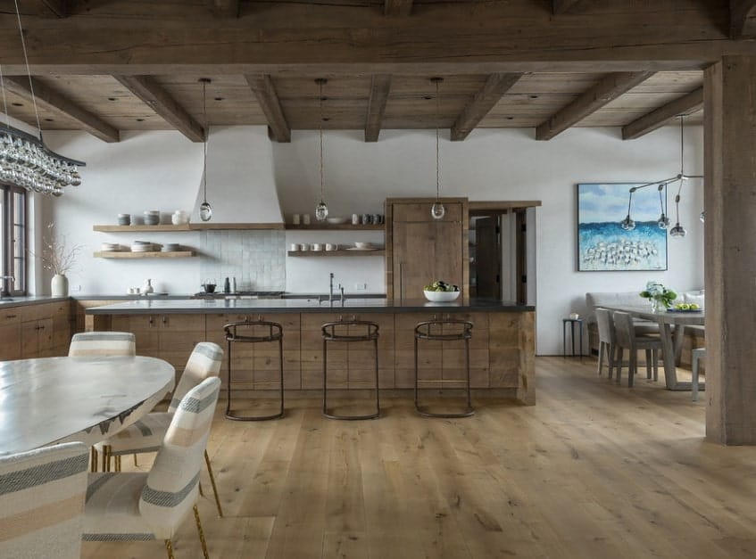 Rustic kitchen with matching hardwood flooring and ceiling lighted by pendant lights. The counters and center island both features smooth dark finished countertops.