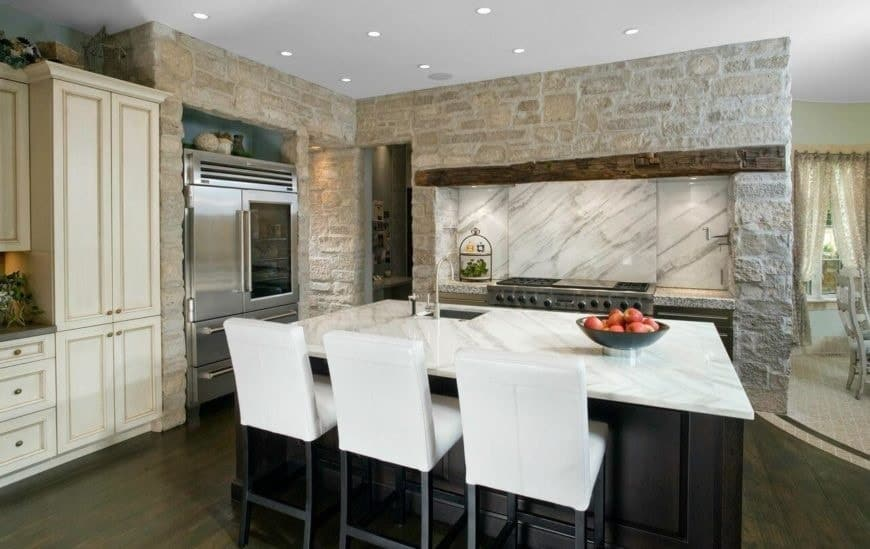 This is a charming Rustic-style kitchen with a large marble-top kitchen island in the middle of the dark hardwood flooring. This is complemented by the bricked and textured stone structure of the cooking area that has white marble backsplash.