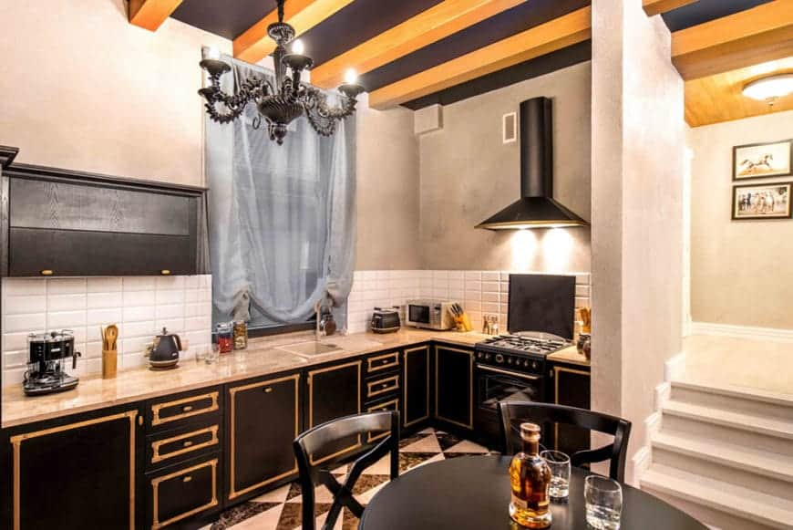 The elegant black ceiling has exposed wooden beams and adorned with a wrought iron black chandelier. This is paired well with the black cabinets of the L-shaped peninsula that has golden trimmings and a beige countertop complemented by the white backsplash tiles.