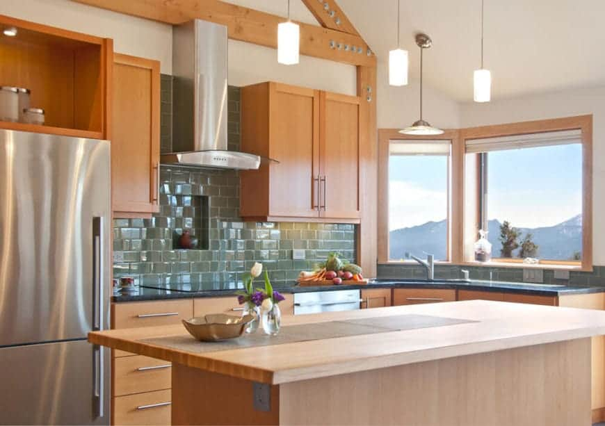 The butcher block countertop of the wooden kitchen island is topped with three small pendant lights. This is augmented by the abundance of natural lighting coming in from the windows above the sink area of the L-shaped peninsula that has a dark green countertop and green tiles for the backsplash.