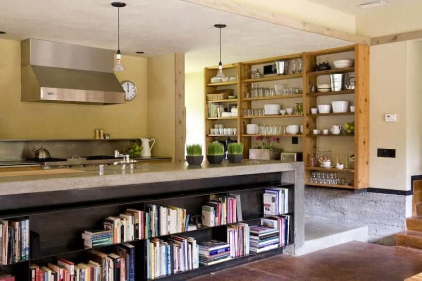 This Rustic-style kitchen has a light gray waterfall concrete countertop for its kitchen island that also houses a book shelf on its outer side. The kitchen peninsula on the far beige wall has a stainless steel countertop that blends with the stove-top oven.