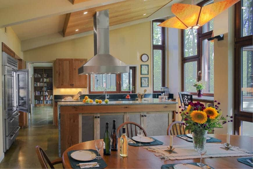 This kitchen is part of a large room that also houses the dining area under its large shed ceiling that is brightened by the several large windows. It also lightens up the wooden island and peninsula that has green countertops and backsplash.
