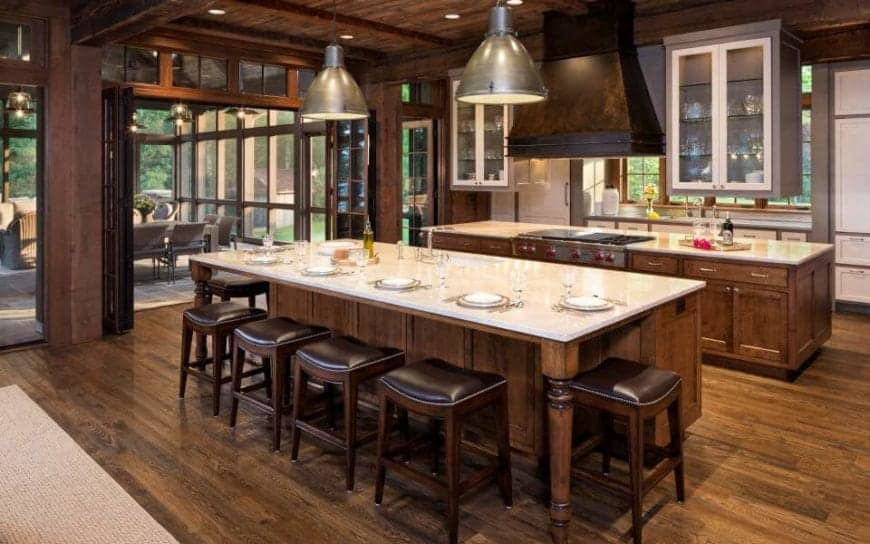 The hardwood flooring of this Rustic-style kitchen matches with the wooden kitchen islands and peninsula as well as the wooden ceiling that has recessed lights and a large vent hood over the cooking area. One of the kitchen islands has an informal dining area on it with wooden stools.