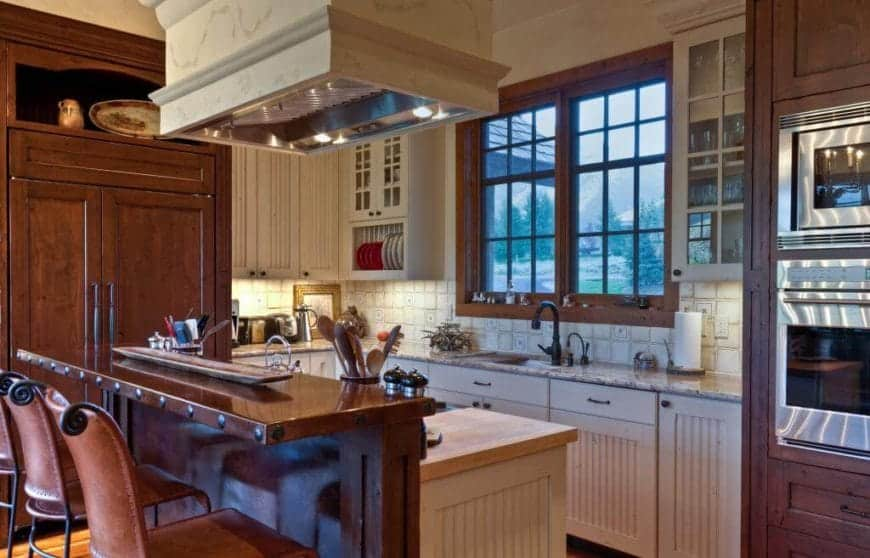 The small wooden kitchen peninsula has a dark brown second level that serves as a breakfast bar paired with wrought iron bar stools with brown leather cushions. The dark brown hue of the bar matches with the cabinetry that flanks the white L-shaped peninsula.