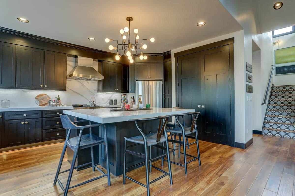 The white ceiling of this Rustic-style kitchen has recessed lights on the sides and a stunning modern chandelier in the middle. This ceiling is contrasted by the dark blue shaker cabinets of the kitchen island and peninsula that houses the modern appliances.
