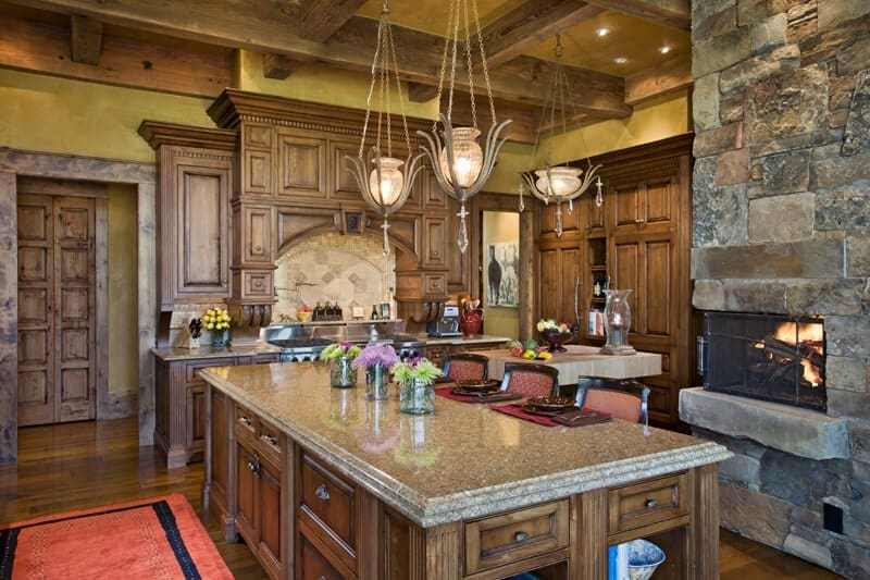 This Rustic-style kitchen is complemented by the large stone structure that houses the fireplace. It provides a gray textured contrast to the wooden cabinetry and the exposed wooden beams of the beige ceiling that supports elegant decorative pendant lights.