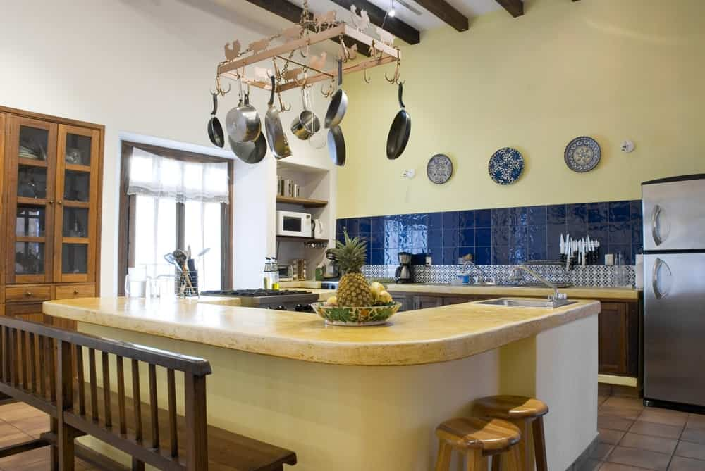 This Rustic-style kitchen has enough space for a large L-shaped kitchen island topped with a metal hanging rack for the pans. This is supported by the high white ceiling with exposed wooden beams that match the cabinets and drawers of the L-shaped peninsula.