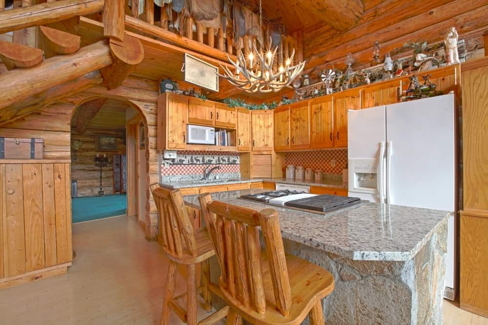 This Rustic-style kitchen has a large white two-door fridge that stands out against the wooden L-shaped peninsula that houses it. This peninsula has a gray marble countertop matching with the stone kitchen island topped with an antler chandelier.