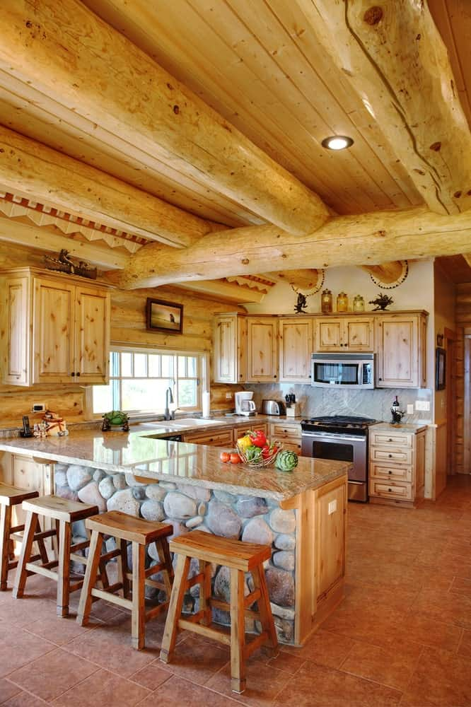 The wooden log cabin-style ceiling has large exposed log beams and recessed lights that shine down on the U-shaped peninsula. This has wooden cabinets and drawers that are complemented by the terracotta flooring and the modern appliances.