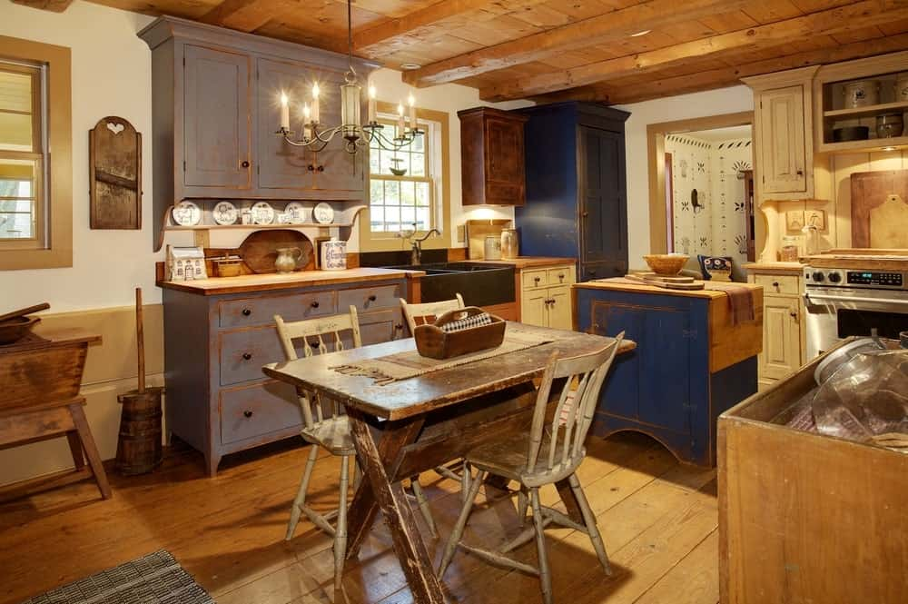 This is a charming kitchen that is mostly made of distressed wooden materials. It can be seen on the cabinets and drawers of the kitchen peninsula and the small island as well as the small informal dining set in the kitchen. This is wonderfully contrasted by the modern stainless steel oven.