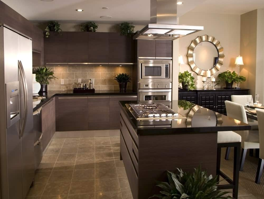 This kitchen has a lovely collaboration of Rustic-style and modern elements. It has a beige marble flooring that complements the dark brown hues of the kitchen island and L-shaped peninsula with black countertops and backsplash that matches the floor.
