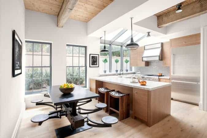 This simple kitchen is bathed with sunlight that comes from the sky lights of the arched ceiling that merges with large glass windows over the sink area of the U-shaped peninsula that has wooden cabinetry matching the hardwood flooring.