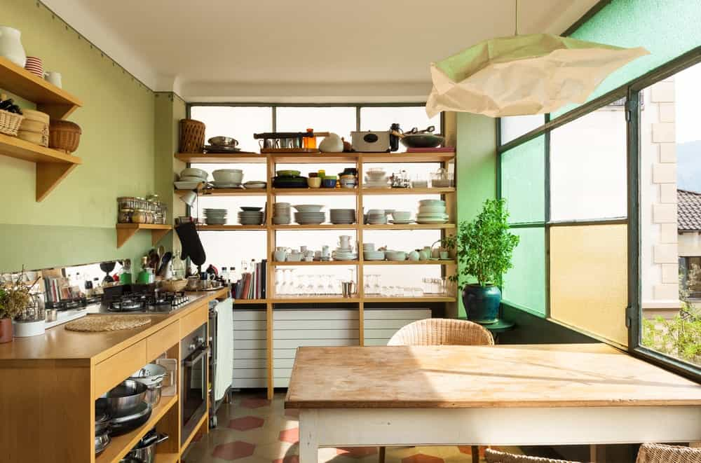 One side of this Rustic-style kitchen has a wall dominated with frosted glass windows that bring in an abundance of natural lighting. This works well with the green walls and the wooden shelves and peninsula contrasted by the gray and terracotta flooring tiles.
