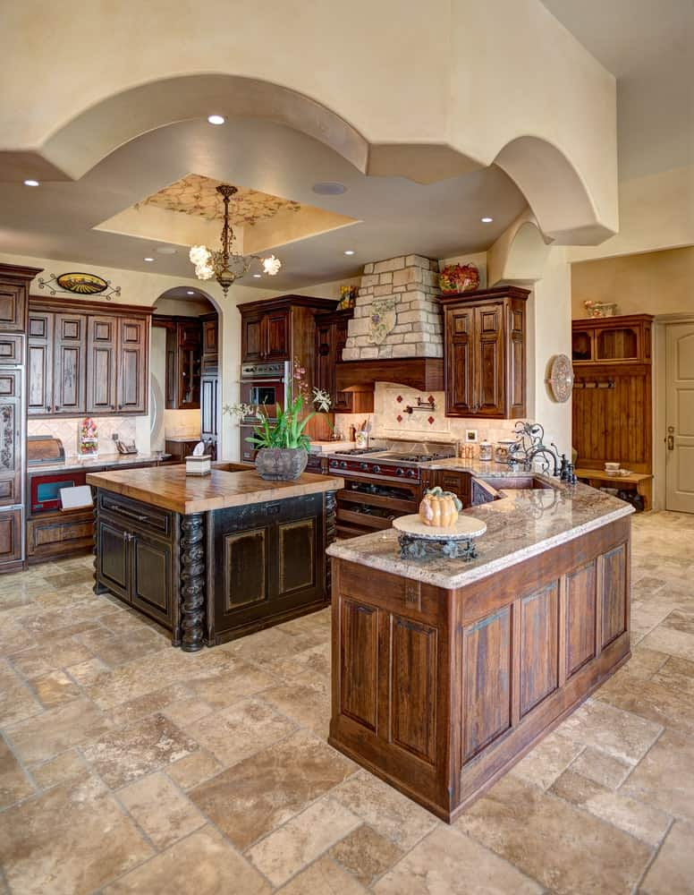 This Rustic-style kitchen makes the most of its small beige marble floor space with a J-shaped peninsula and a small kitchen island both having the same wooden hue. The island is topped with a butcher block countertop and a beautiful decorative chandelier.