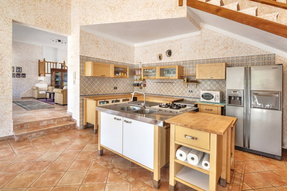 The light terracotta flooring provides an earthy complement to the wooden kitchen island and kitchen peninsula with an L shape and matches with the floating wooden cabinets that stand out against the complex pattern of the wall tiles.