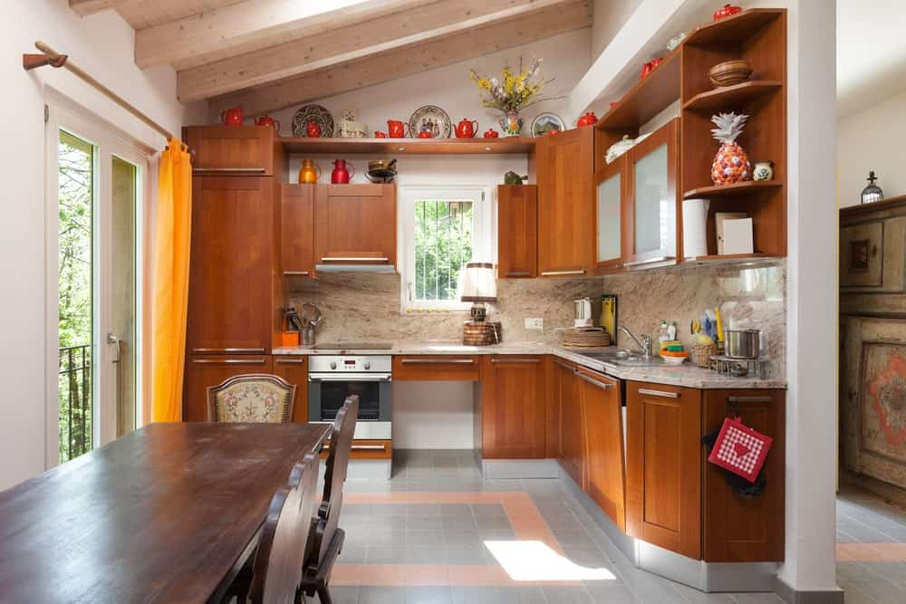 This is a bright kitchen mostly due to the natural lights coming from the skylights of the wooden ceiling with exposed wooden beams as well as the glass sliding door. This works well with the dark wooden cabinetry of L-shaped peninsula.