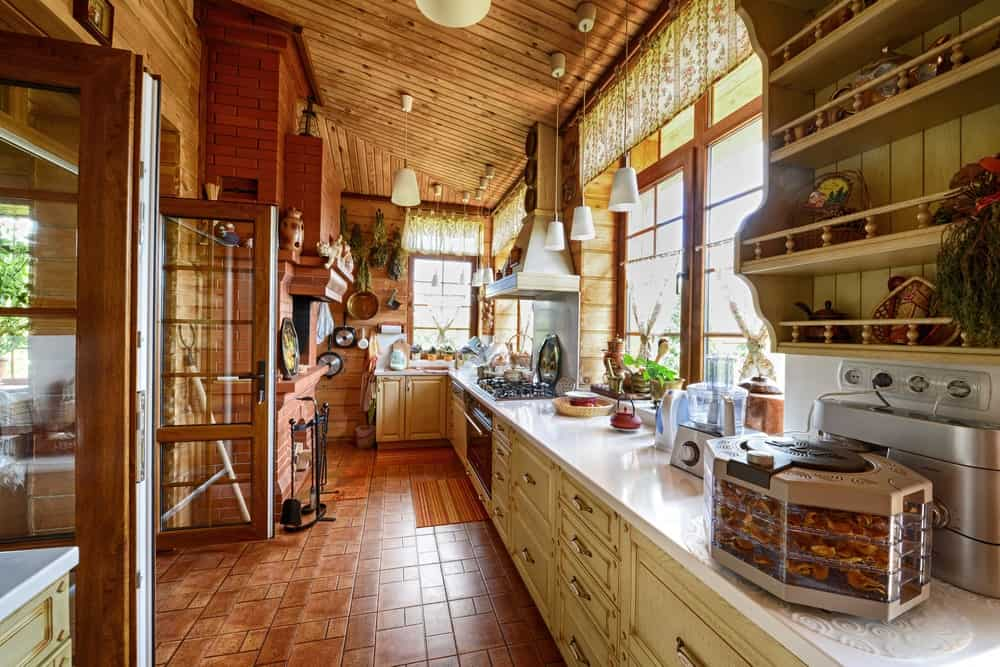 This long hallway-like kitchen has no space for a kitchen island but it has a long L-shaped kitchen peninsula that has beige cabinets and drawers that are complemented by the terracotta flooring tiles matching the bricks of the fireplace across from the peninsula.