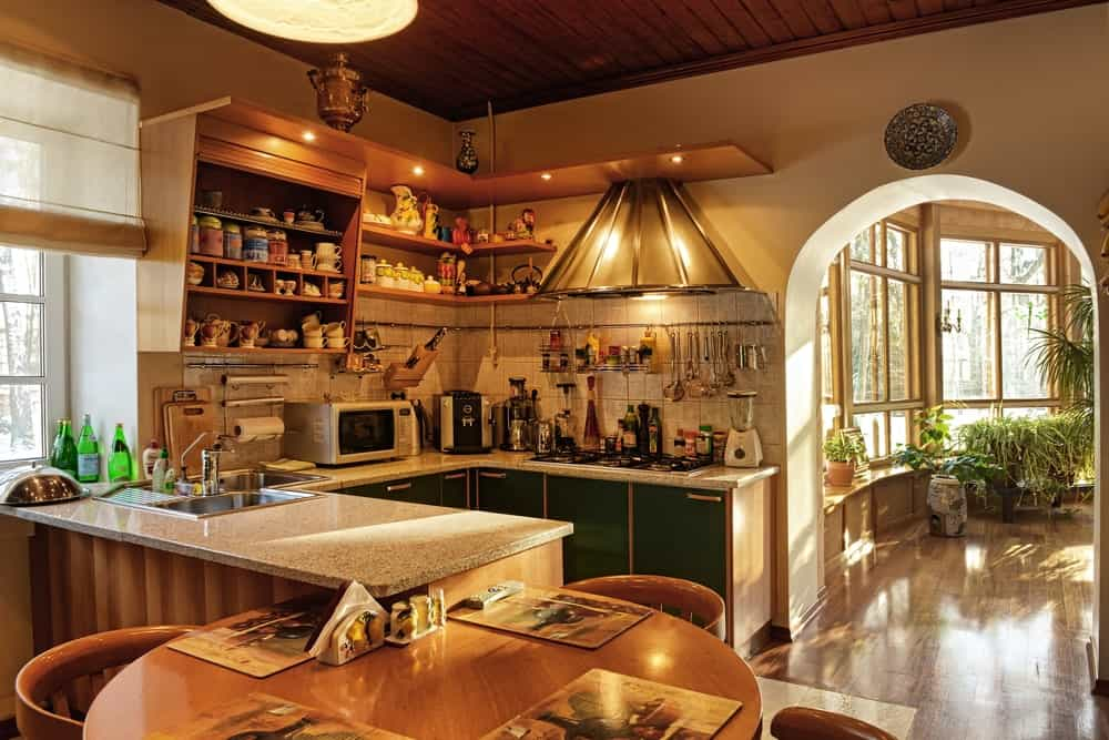 The dark wooden ceiling of this small Rustic-style kitchen has a shiplap plank finish and augmented by the warm yellow lights scattered across the kitchen. It also enhances the the floating cabinets and shelves as well as the small U-shaped peninsula.