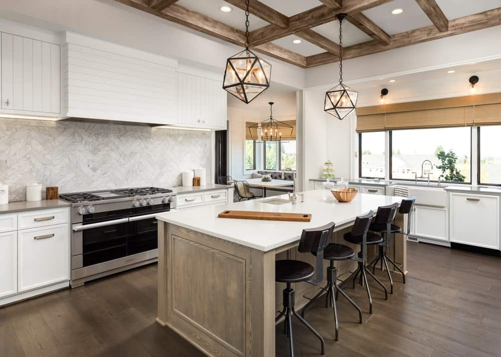 The wooden kitchen island matches with the hardwood flooring and the exposed wooden beams of the white ceiling. From this ceiling hangs a couple of decorative lantern-like pendant lights. This stands out against the background of white kitchen peninsulas with white marble backsplash.